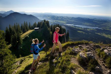 Erlebnisreiche Sommerfrische im Allgäu. Auf den Allgäuer Gipfeln bläst den Wanderern ein erfrischender Wind um die Nase.